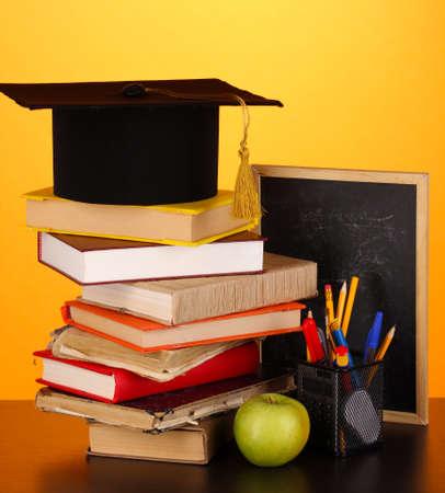 licenciatura: Libros y gorra magister en contra de la junta escolar en la mesa de madera sobre fondo amarillo Foto de archivo