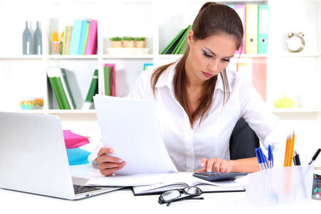 Young pretty business woman with notebook in office Stock Photo - 16546522
