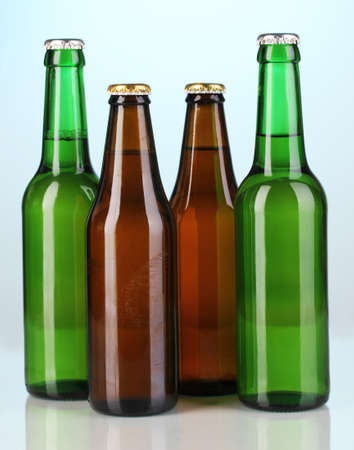 Coloured glass beer bottles on blue background photo