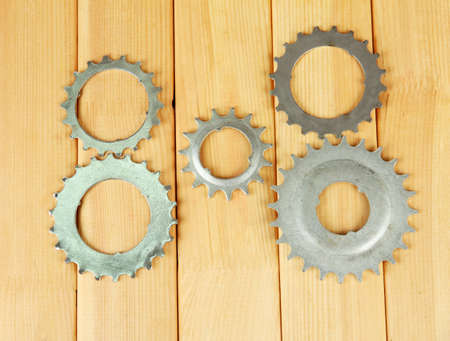 Metal cogwheels on wooden background photo