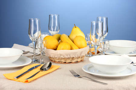 Table setting in white and yellow tones on color  background photo