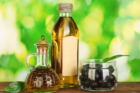 Olive oil bottle and small decanter on green background photo
