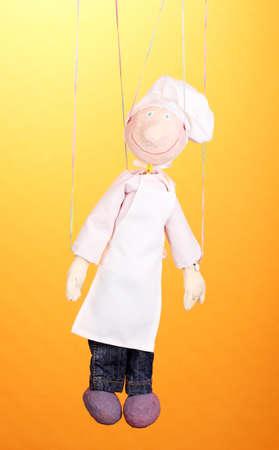 marioneta de madera: Marioneta de madera como cocinero en fondo naranja