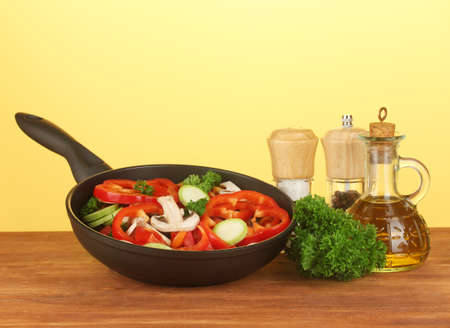 frying pan with vegetables on yellow background Stock Photo
