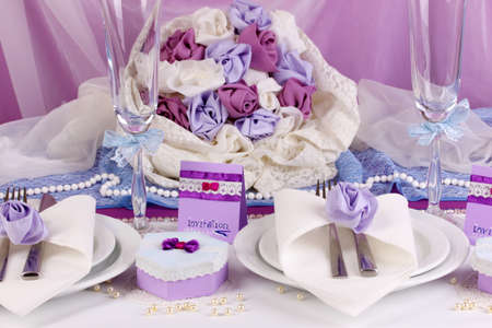 restaurant setting: Serving fabulous wedding table in purple color on white and purple fabric background Stock Photo
