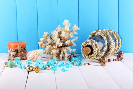 Decor of seashells on wooden table on blue wooden background photo