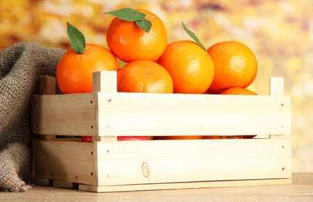 Ripe tasty tangerines with leaves in wooden box on table on orange background photo