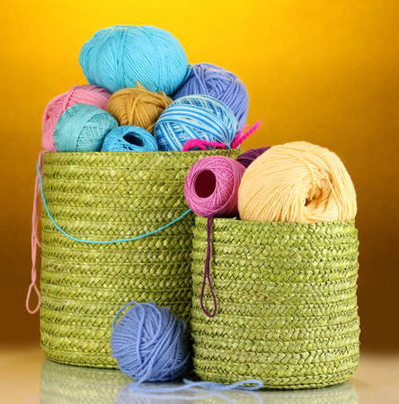 Colorful yarn for knitting in green basket on orange background photo