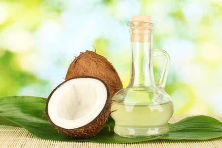 coconut oil: decanter con olio di cocco e noci di cocco su sfondo verde