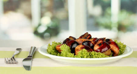 roasted chestnuts with lettuce in the plate on the tablecloth close-up photo