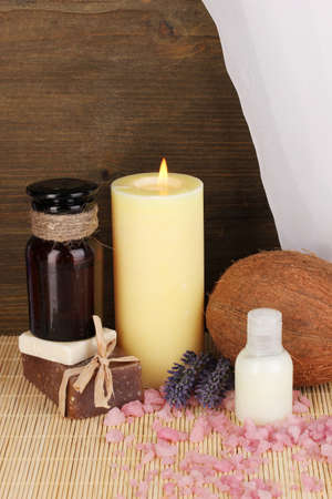 Bottle with aromatic oils with accessories for relaxation close-up on wooden table on wooden background photo
