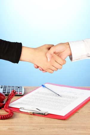 cuadro sinoptico: d�ndose la mano tras la firma del acuerdo, sobre un fondo azul