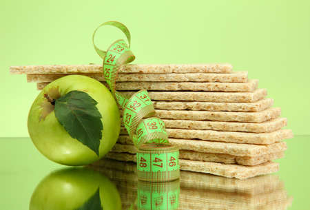 galettes: tasty crispbread, apple and measuring tape, on green background