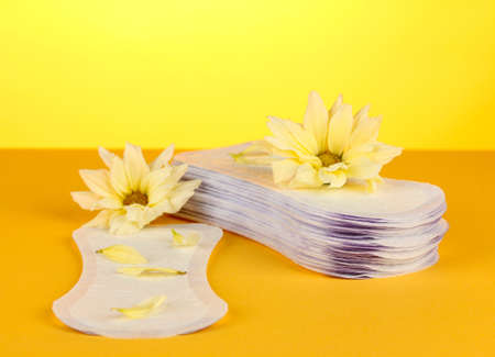personally: daily panty liners and yellow flowers on orange background close-up Stock Photo