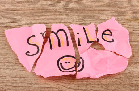 table scraps: Torn paper with words Smile close-up on wooden table Stock Photo