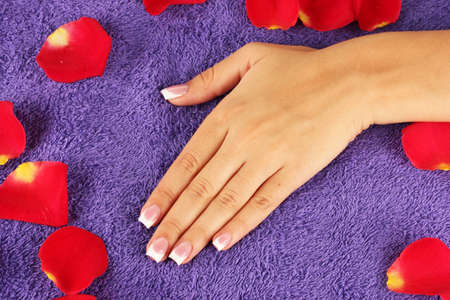 womans hand on purple terry towel, close-up photo