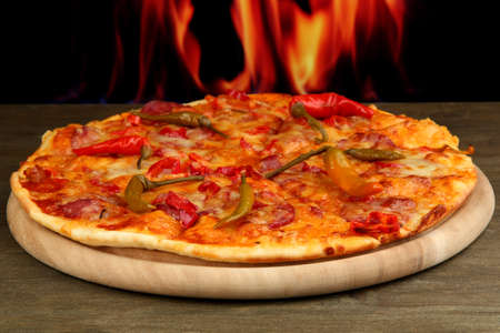 Tasty pepperoni pizza on wooden board on flame background photo