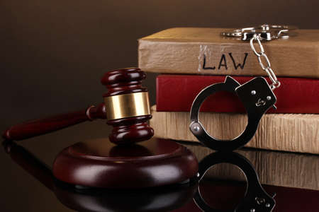 Gavel, handcuffs and books on law isolated on black close-up photo