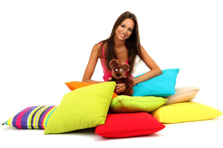 beautiful young girl and fluffy bear with pillows isolated on white photo