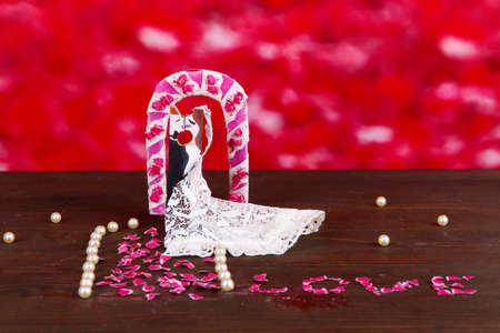 reciprocity: Decorative married loving couple on wooden table on red background Stock Photo