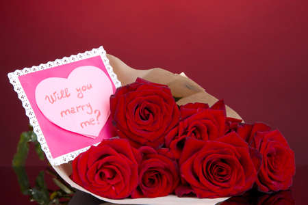 reciprocity: Beautiful bouquet of red roses with valentine on red background Stock Photo
