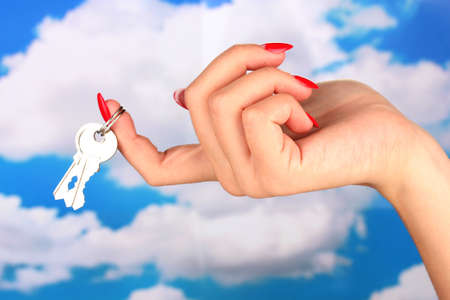 Hand with key on sky background photo