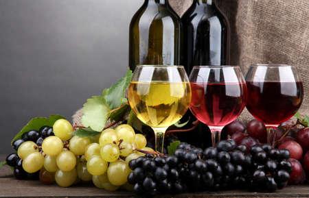 white wine bottle: Botellas y vasos de vino y uvas sobre fondo gris