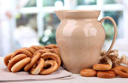 boublik: jar of milk, tasty bagels and spikelets on table