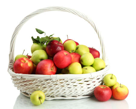 juicy apples with green leaves in basket, isolated on white photo