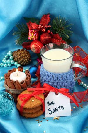 galletas de jengibre: Galletas para Santa: Imagen conceptual de jengibre galletas, la leche y la decoraci�n de Navidad sobre fondo azul Foto de archivo