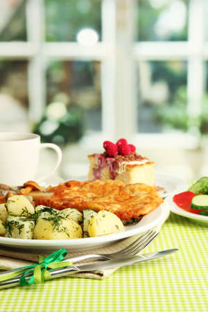 Roast chicken cutlet with boiled potatoes and cucumbers, cup of tea and dessert on green table cloth in cafe interior photo