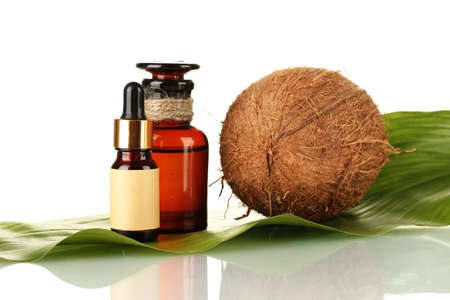 coconut oil in bottles with coconuts on white background Stock Photo - 16449507