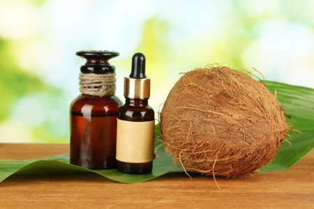 coconut oil in bottles with coconuts on green background photo