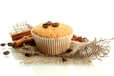 tasty muffin cake on burlap, spices and coffee seeds, isolated on white photo