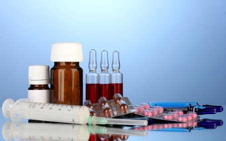 medical ampules, bottles, pills and syringes on blue background photo