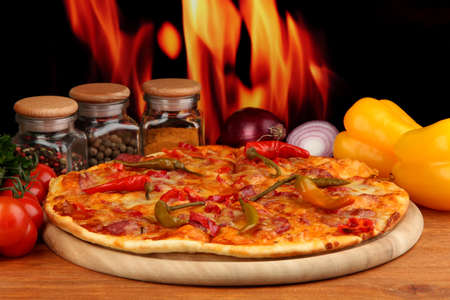 Tasty pepperoni pizza with vegetables on wooden board on flame background Stock Photo - 16469411