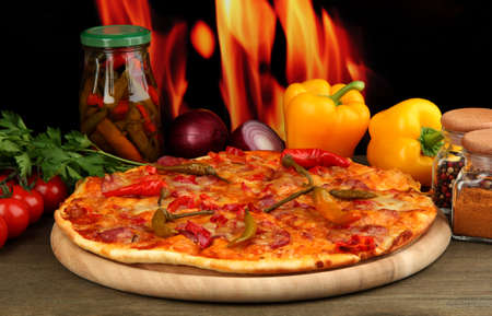 Tasty pepperoni pizza with vegetables on wooden board on flame background Stock Photo - 16469392