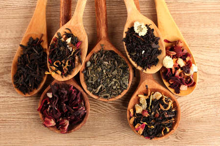 pile of leaves: assortment of dry tea in spoons, on wooden background