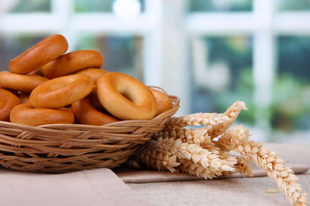 spikelets: tasty bagels in basket and spikelets on table Stock Photo
