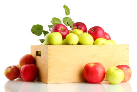 juicy apples with green leaves in wooden crate, isolated on white photo