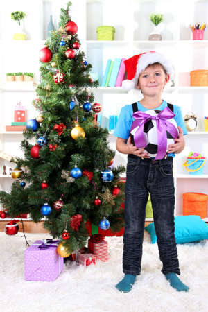 Little boy in Santa hat stands near Christmas tree with football ball Stock Photo - 16547304