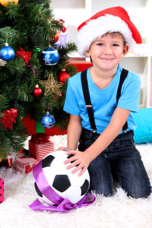 Little boy in Santa hat sits near Christmas tree with football ball Stock Photo - 16547296