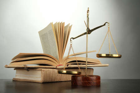 law scale: Gold scales of justice and books on grey background