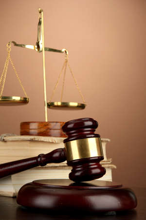 justice balance: Golden scales of justice, gavel and books on brown background Stock Photo