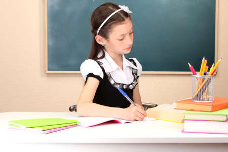 little schoolchild in classroom write in notebook photo