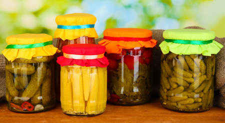 Jars with canned vegetables on green background close-up Stock Photo - 16500627