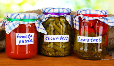 Jars with canned vegetables on green background close-up Stock Photo - 16500686