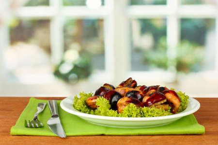 roasted chestnuts with lettuce in the plate on wooden table close-up Stock Photo - 16500633