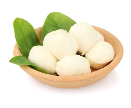queso blanco: queso mozzarella con albahaca verde en la placa de arcilla aislado en blanco