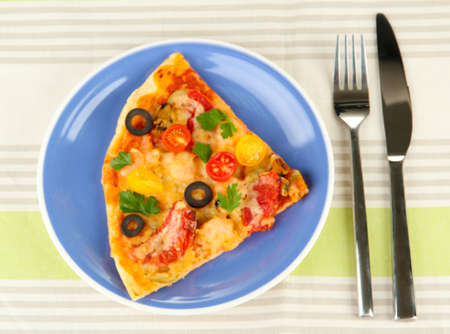 plate with a slice of delicious pizza on tablecloth close-up Stock Photo - 16500232